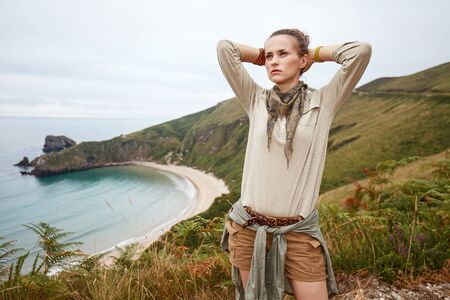Into the wild in Spain. relaxed healthy woman hiker looking into the distance in front of ocean view landscape
