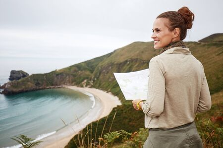 Into the wild in Spain. Seen from behind happy adventure woman hiker with map looking into the distance in front of ocean view landscape