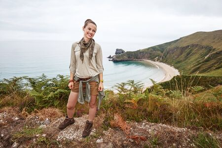 Into the wild in Spain. Full length portrait of smiling adventure woman hiker looking aside in front of ocean view landscape Stock Photo