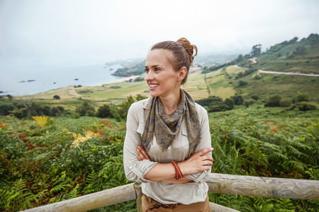 Into the wild in Spain. smiling adventure woman hiker looking aside in front of ocean view landscape