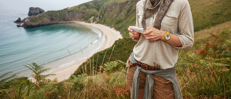 Into the wild in Spain. happy adventure woman hiker writing sms in front of ocean view landscape Stock Photo