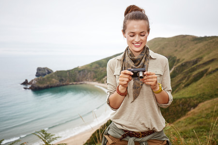 Into the wild in Spain. smiling adventure woman hiker viewing photos on camera in front of ocean view landscape Stock Photo