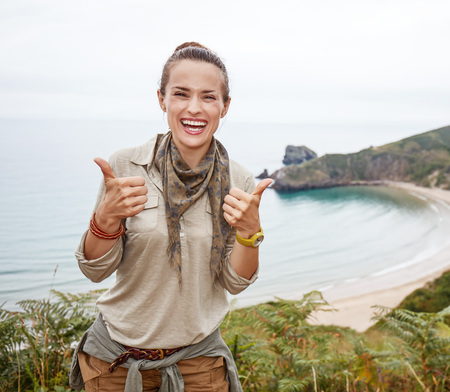 Into the wild in Spain. Portrait of happy healthy woman hiker showing thumbs up in front of ocean view landscape