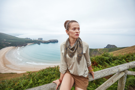 Into the wild in Spain. Portrait of adventure woman hiker in front of ocean view landscape