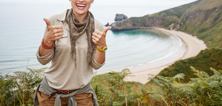 Into the wild in Spain. Closeup on happy healthy woman hiker showing thumbs up in front of ocean view landscape