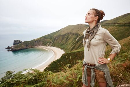 Into the wild in Spain. relaxed active woman hiker in front of ocean view landscape Stock Photo