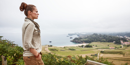 Into the wild in Spain. active woman hiker looking into the distance while standing in the front of ocean view landscape
