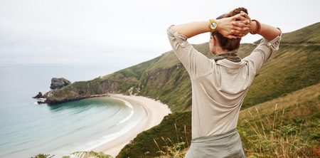Into the wild in Spain. Seen from behind active woman hiker enjoing ocean view landscape Stock Photo