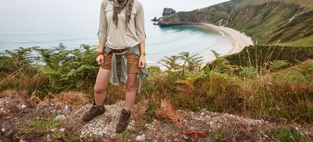 Into the wild in Spain. Closeup on smiling adventure woman hiker looking aside in front of ocean view landscape Stock Photo