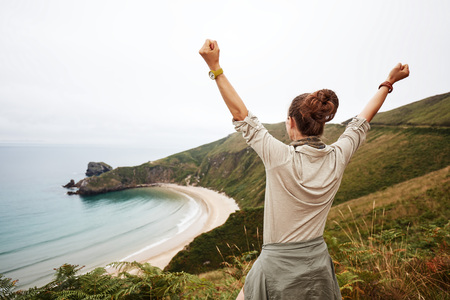 Into the wild in Spain. Seen from behind healthy woman hiker rejoicing in front of ocean view landscape