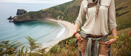 Into the wild in Spain. active woman hiker looking into the distance in front of ocean view landscape