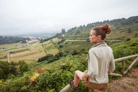 Into the wild in Spain. Seen from behind healthy woman hiker enjoying beautiful landscape view