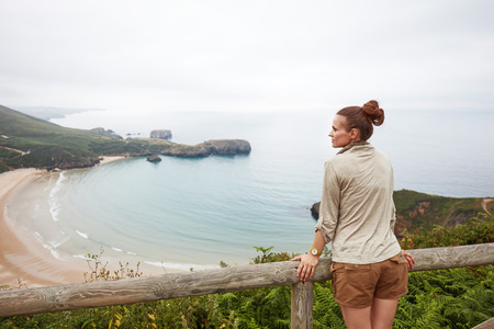Into the wild in Spain. Seen from behind healthy woman hiker looking at ocean view landscape