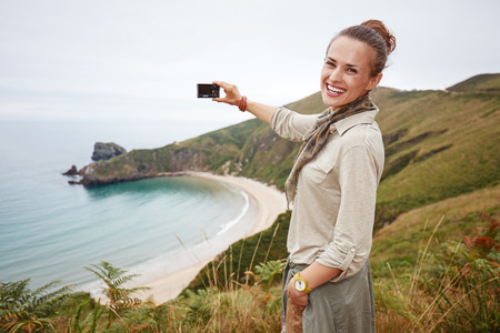 Into the wild in Spain. Portrait of smiling active woman hiker taking photo with digital camera in front of ocean view landscape