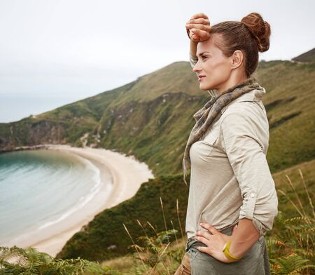 Into the wild in Spain. Portrait of adventure woman hiker looking into the distance in front of ocean view landscape Stock Photo