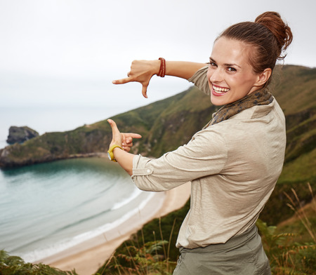 Into the wild in Spain. happy adventure woman hiker framing with hands in front of ocean view landscape Stock Photo