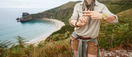 Into the wild in Spain. Closeup on smiling healthy woman hiker showing hashtag gesture in front of ocean view landscape