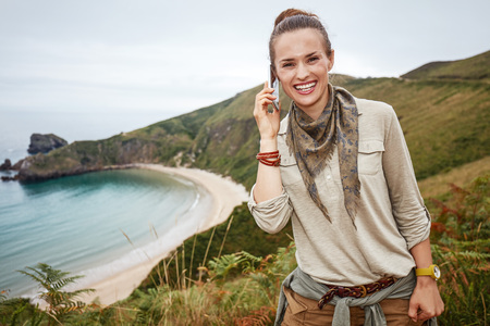 Into the wild in Spain. Portrait of smiling healthy woman hiker talking on a cell phone in front of ocean view landscape