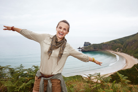 Into the wild in Spain. Portrait of smiling healthy woman hiker having fun time in front of ocean view landscape
