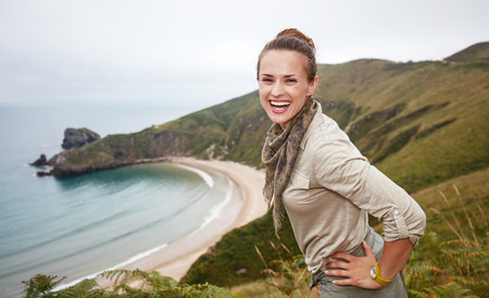 Into the wild in Spain. Portrait of happy adventure woman hiker in front of ocean view landscape Stock Photo