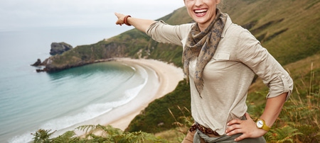 Into the wild in Spain. smiling active woman hiker pointing on something in front of ocean view landscape Stock Photo