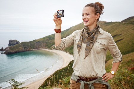 Into the wild in Spain. adventure woman hiker taking photo with digital camera in front of ocean view landscape