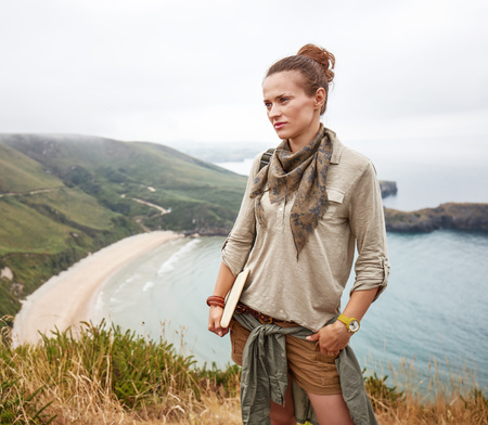 Into the wild in Spain. adventure woman hiker with tablet PC in front of ocean view landscape