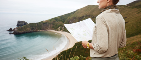 Into the wild in Spain. Closeup on healthy woman hiker with map looking into the distance in front of ocean view landscape