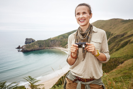 Into the wild in Spain. adventure woman hiker with digital camera looking into distance in front of ocean view landscape