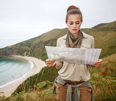 Into the wild in Spain. adventure woman hiker looking at the map in front of ocean view landscape