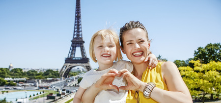 shaped hands: Having fun time near the world famous landmark in Paris. smiling mother and daughter showing heart shaped hands in Paris, France