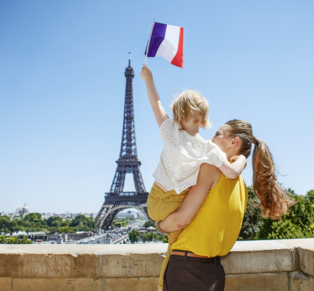 Having fun time near the world famous landmark in Paris. Seen from behind mother and child travellers rising flag in Paris, France