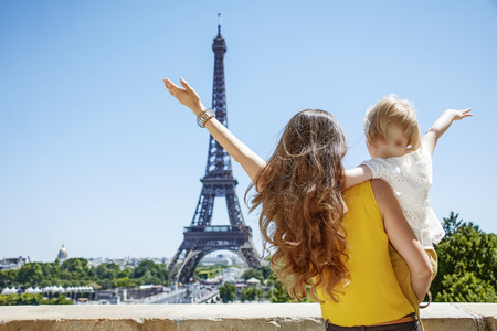 Having fun time near the world famous landmark in Paris. Seen from behind mother and daughter travellers rejoicing and looking at Eiffel tower against Eiffel tower Stock Photo