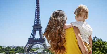 Having fun time near the world famous landmark in Paris. Seen from behind mother and child looking at Eiffel tower in the front of Eiffel tower