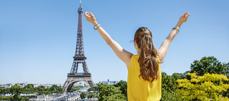 Having fun time near the world famous landmark in Paris. Seen from behind young woman in bright blouse rejoicing in Paris, France