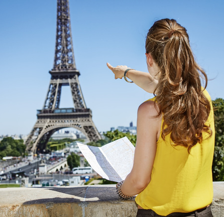 anonym: Having fun time near the world famous landmark in Paris. Seen from behind young woman in bright blouse holding map and pointing on Eiffel tower Stock Photo