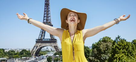 rejoicing: Having fun time near the world famous landmark in Paris. Portrait of smiling young woman in bright blouse rejoicing in the front of Eiffel tower Stock Photo
