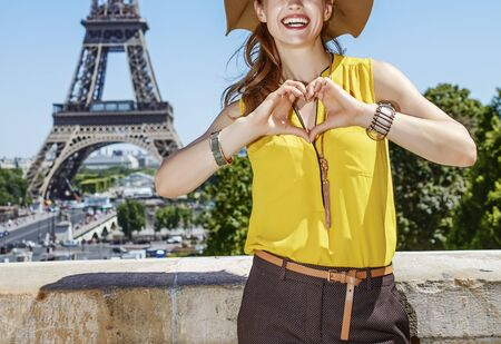 shaped hands: Having fun time near the world famous landmark in Paris. Closeup on smiling young woman in bright blouse showing heart shaped hands in Paris, France Stock Photo