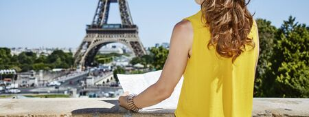 Having fun time near the world famous landmark in Paris. Closeup on young woman in bright blouse sightseeing in the front of Eiffel tower
