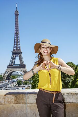 shaped hands: Having fun time near the world famous landmark in Paris. Portrait of smiling young woman in bright blouse showing heart shaped hands in Paris, France
