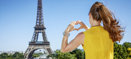 Having fun time near the world famous landmark in Paris. Seen from behind young woman in bright blouse showing heart shaped hands in Paris, France