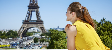 Having fun time near the world famous landmark in Paris. Seen from behind young woman in bright blouse looking into the distance against Eiffel tower 版權商用圖片 - 62268325
