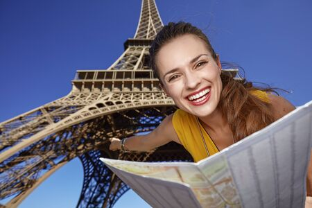 touristy: Touristy, without doubt, but yet so fun. Portrait of smiling young woman holding map and pointing in the front of Eiffel tower in Paris, France Stock Photo