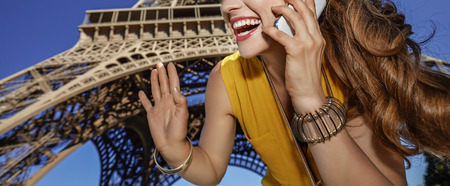 touristy: Touristy, without doubt, but yet so fun. smiling young woman speaking on a cell phone and hand waving against Eiffel tower in Paris, France Stock Photo