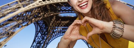 shaped hands: Touristy, without doubt, but yet so fun. Closeup on smiling young woman showing heart shaped hands in the front of Eiffel tower in Paris, France Stock Photo
