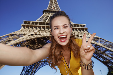 touristy: Touristy, without doubt, but yet so fun. happy young woman taking selfie and showing victory against Eiffel tower in Paris, France