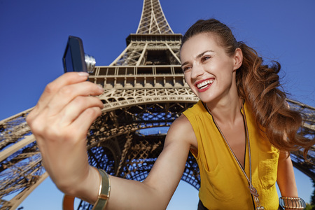 touristy: Touristy, without doubt, but yet so fun. smiling young woman taking selfie with digital camera against Eiffel tower in Paris, France