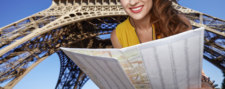 Touristy, without doubt, but yet so fun. Closeup on happy young woman exploring attractions in the front of Eiffel tower in Paris, France Stock Photo