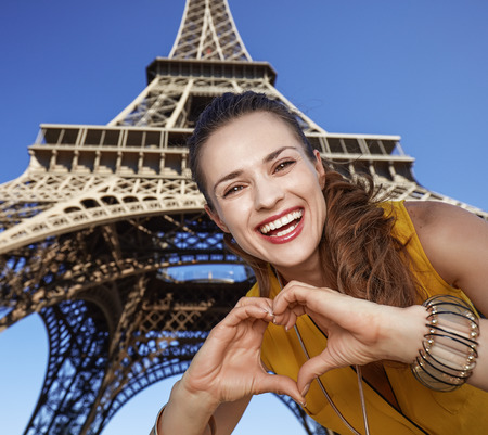shaped hands: Touristy, without doubt, but yet so fun. Portrait of smiling young woman showing heart shaped hands in the front of Eiffel tower in Paris, France Stock Photo