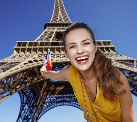 touristy: Touristy, without doubt, but yet so fun. Portrait of happy young woman rising flag against Eiffel tower in Paris, France Stock Photo